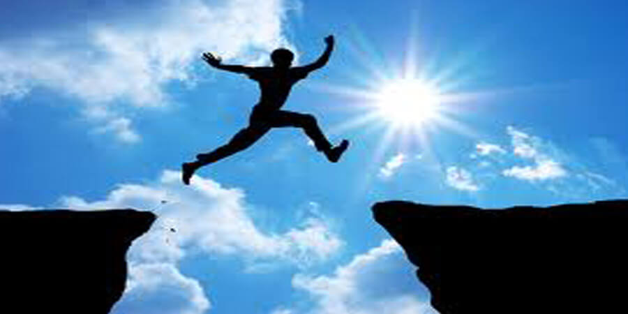 Inspirational Career Coaching. Man jumping across a ledge against the sun.