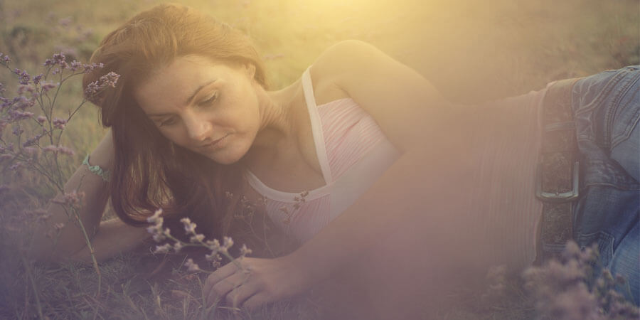 Self Talk in Relationships. Girl laying in grass with a wild flower thinking.